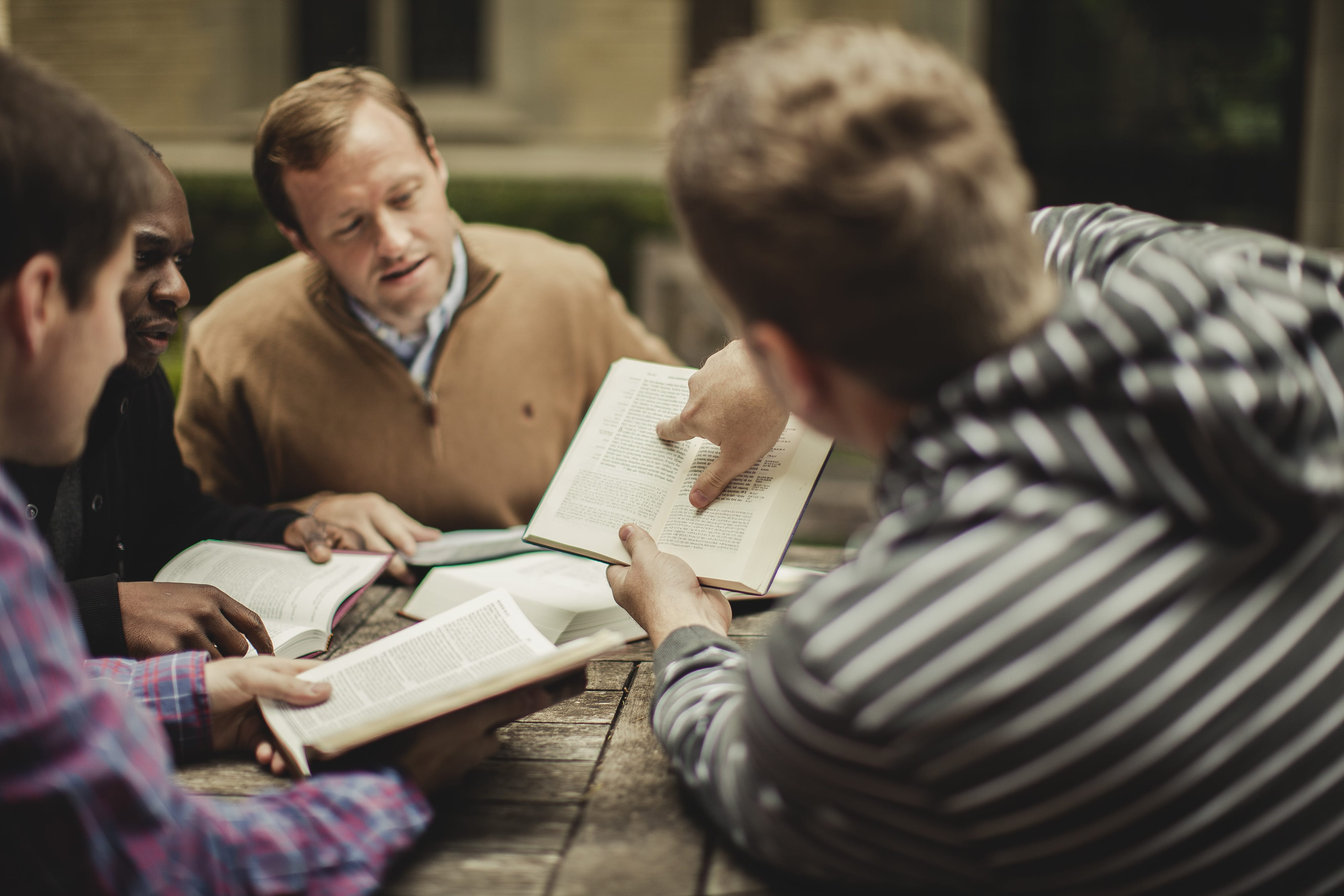 Men studying minister training book to become ordained ministers